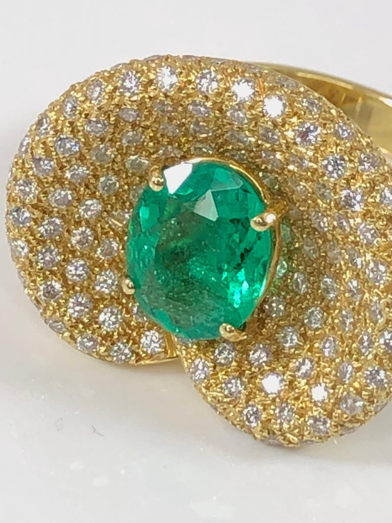 This beautiful S.Georgios designer ring is all handmade in our workshop in Greece from 18 Karat Yellow Gold. The ring features 2.44 Carat oval cut Emerald center and 1.68 Carat brilliant cut White Diamond pave background. Size: 7 3/4 (Can be custom