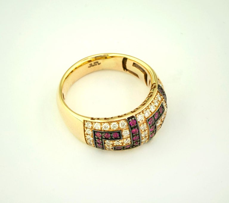 This S.Georgios designer 18 Karat Yellow Gold Greek Key Band Ring is all handmade in a unique two-tone look. The gorgeous band features brilliant cut diamonds forming the Greek Key design total weight of 0.52 Carat, and natural Rubys total weight of