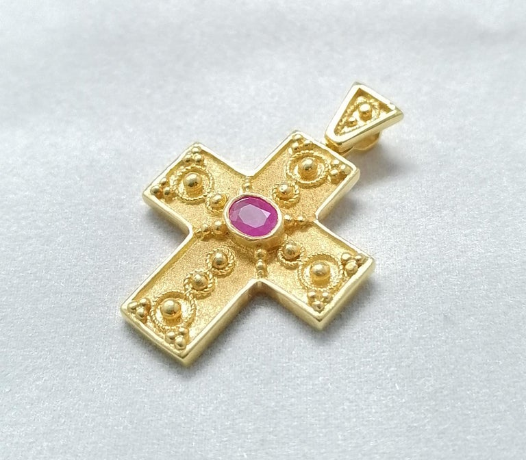 This S.Georgios solid 18 Karat Yellow Gold geometric Cross pendant is beautifully handmade and microscopically decorated Byzantine-style bead granulation work. This gorgeous cross features an oval-cut natural Ruby total weight 0.37 Carat and is