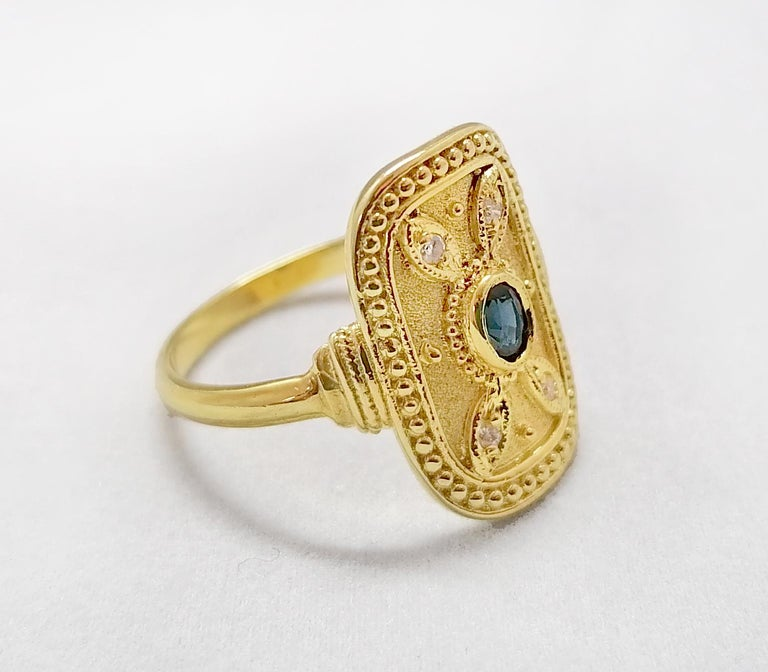 This S.Georgios designer ring is handmade from solid 18 Karat Yellow Gold and is microscopically decorated with Byzantine-style granulation work creating a stunning art piece. This beautiful long ring features an elegant center oval-cut natural