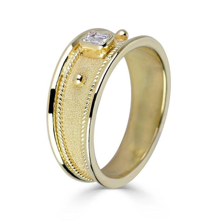 This S.Georgios designer ring in solid 18 Karat Yellow Gold all handmade with Byzantine workmanship and a unique velvet look on the background. This Unisex gorgeous ring features an emerald-cut White Diamond VVS1 -F color the weight of 0.20 Carat.