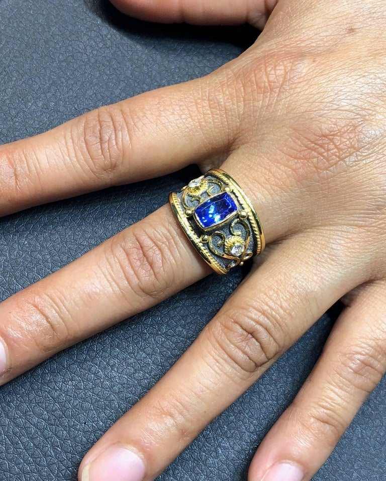 One of a kind S.Georgios Hand Made 18 Karat Yellow Gold Ring with 2 Brilliant Cut White Diamonds total weight of 0.18 Carat and a center 1.85 Carat Cushion Cut Natural Tanzanite. The ring is richly decorated with Byzantine era style granulation work