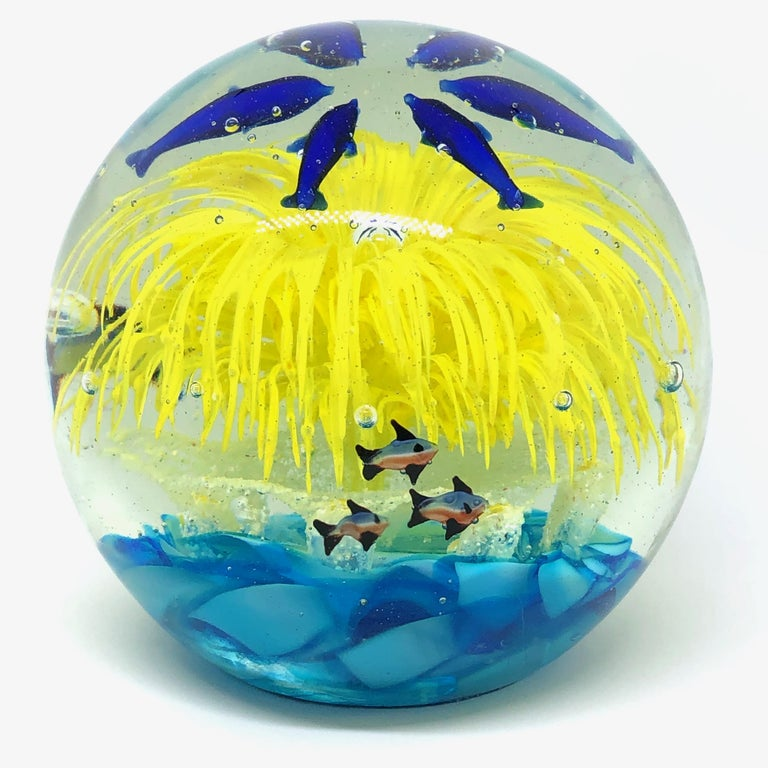 Beautiful Murano hand blown aquarium Italian art glass paper weight. Showing some blue dolphins and fishes with a Coral Reef inside, floating on controlled bubbles. Colors are a blue, yellow and clear. A beautiful nice addition to your desktop or as