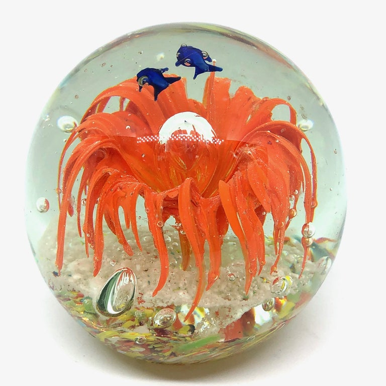 Beautiful Murano hand blown aquarium Italian art glass paper weight. Showing some blue fishes in a coral reef, floating on controlled bubbles. Colors are a blue, orange and clear. A beautiful nice addition to your desktop or as a decorative piece in