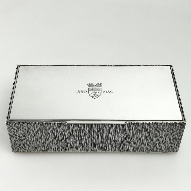 A gorgeous solid silver cigar box by the acclaimed post war Silversmith Gerald Benney. An elegant rectangular box with a bark effect on the sides and underside. The lid is polished silver with a small crests and the dates 1880-1980. The interior is