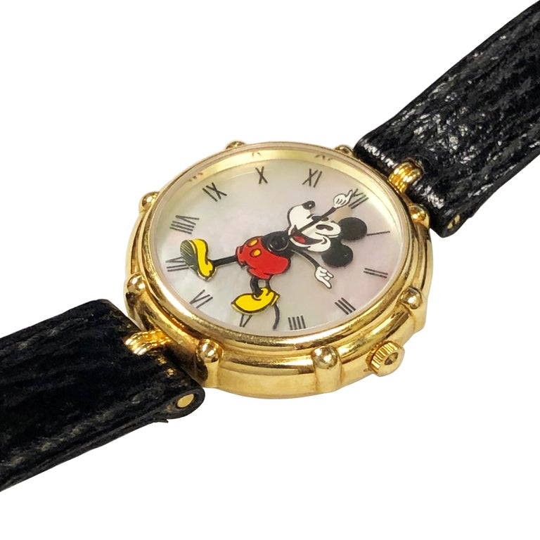 Circa 2000 Gerald Genta Mickey Mouse Wrist Watch, 30 MM 18K Yellow Gold 2 piece water resistant case. Quartz Movement, mother of Pearl Dial with black Roman numerals and an Enamel Mickey Mouse with Animated Hands.  Original Black Stitched Grain