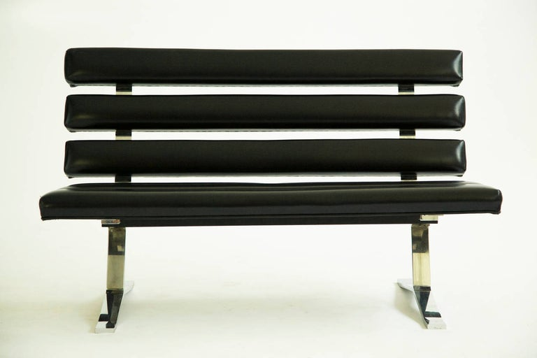 Gerald McCabe settee or bench, solid chrome-plated steel frame with black vinyl seat and back composed of individual sections.