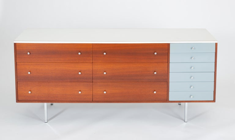 A late 1950s custom-built dresser by California designer and craftsman Gerald McCabe has a walnut body with a white laminate top. The case contains six large, deep drawers with walnut panels next to a single stack of six smaller drawers painted in a