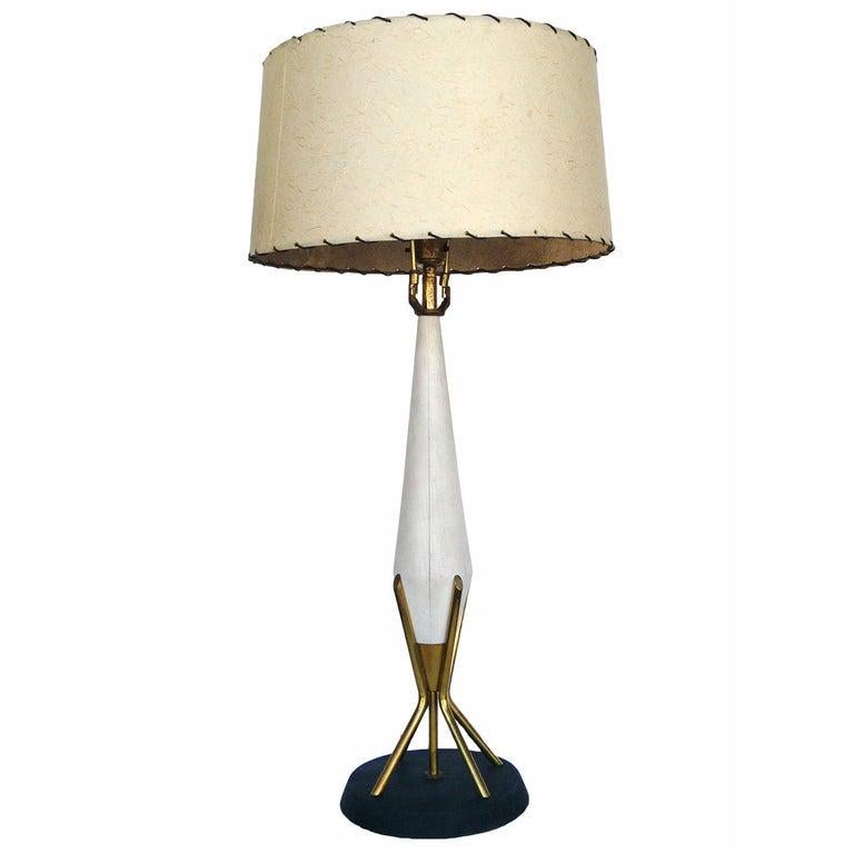 This midcentury Thurston style table lamp has a modern elegance. The white painted sculptural wood center, bright brass accents, and atomic age fiberglass shade all meet to a black rounded base for a streamlined design serene only the 1950s could