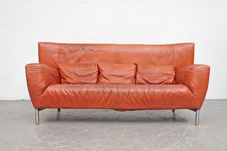 Gerard van den Berg for Montis terracotta leather sofa with nice natural patina. Tubular frame with wooden foot caps and 3 matching pillows. In original condition with a small tear and puncture on the back. Wear consistent with its age and usage.