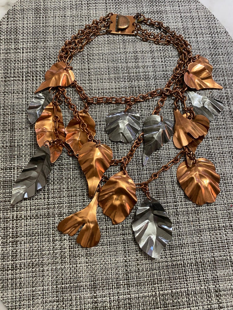 Rare and unique Gerda Lynggaard leaves necklace. What a statement jewelry.  Necklace has three strands of chain and layer with bronze and silver leaf pendant. see measurement on picture attached.