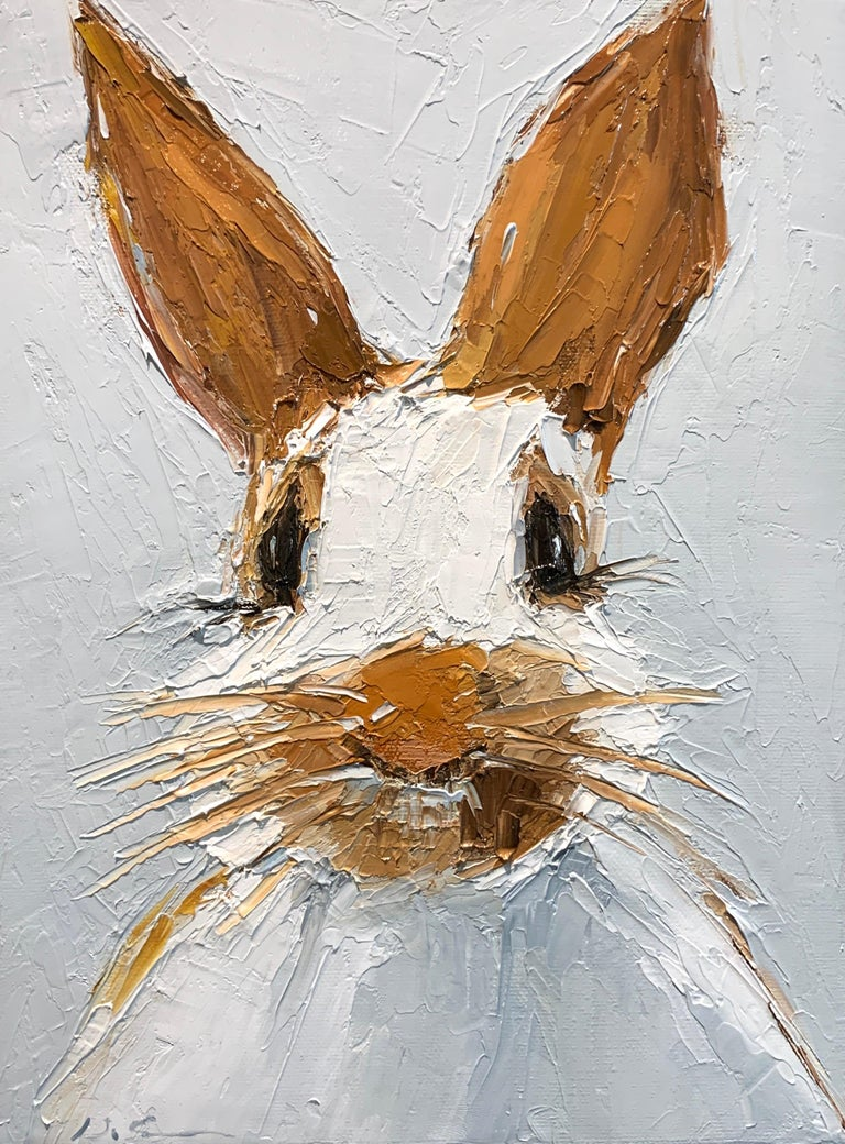 This painting by Geri Eubanks depicts a rabbit facing forward with a creamy white background and touches of orange, brown, black and blue painted on the rabbit.  The artist adds layers and layers of oil paint to achieve very apparent texture, she
