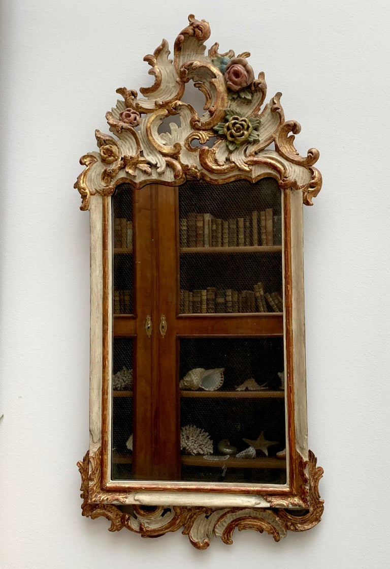 Very charming German 18th century period Rococo mirror. Beautifully carved with c-scrolls and flower buds, white and polychrome painted. Antique mirror plate and orginal back.