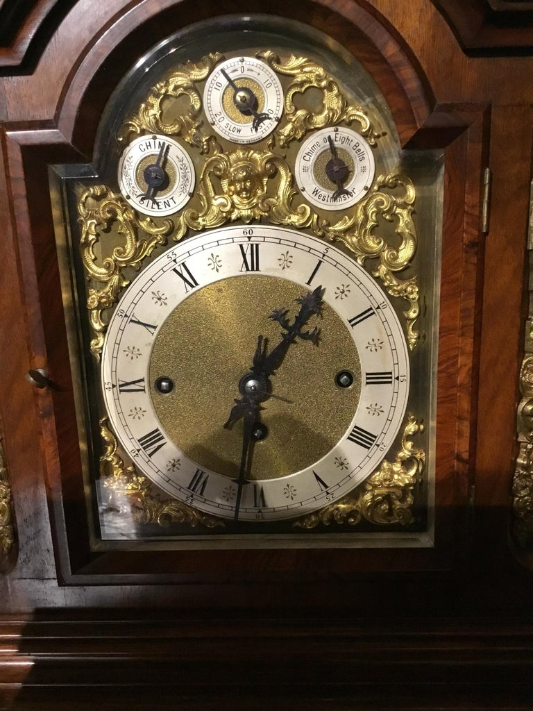 Very handsome walnut clock with ormolu mounts on the sides, front corners and paw feet. Urn type finials grace the top center and top corners. Beveled glass front opening to a face With Roman numerals. Has original key and pendulum.