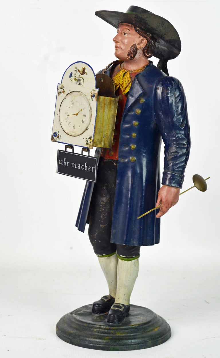 A German Black Forest polychrome painted tole figure of a clock maker in traditional dress, carrying a shield clock in his right and a pendulum in his left hand. Under the clock a sign bearing the inscrition in German 'Uhr Macher'. An interesting