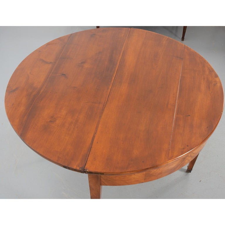 This is a great Biedermeier-style demilune table from Germany. The table has a solid, folding top with brass hinges sitting over a book-matched apron. A fourth leg is attached to a drawer that pulls out to support the top and has a felt edge as not