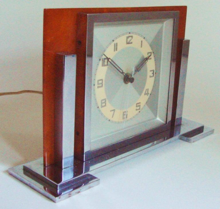 This strongly designed German Art Deco electric desk clock is brilliant in its simplicity. It features a stepped chrome base, chrome bezel and two chrome pillars flanking this bezel. The clock motor housing is totally chrome plated and it is