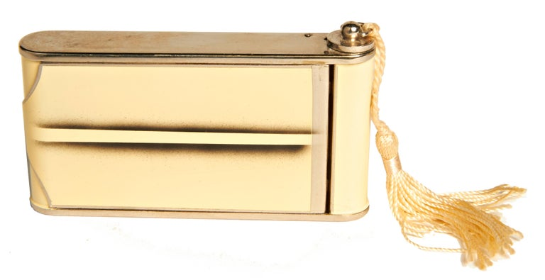 This beautifully designed German Art Deco camera compact/minaudiere features ecru colored enamel banded in chrome on the front with two gradated black enamel bands to the back. On one side it has a large lift-top compact with mirror and complete