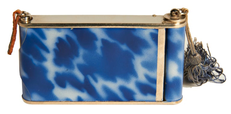 This beautifully designed German Art Deco camera compact/minaudiere features blue tortoiseshell enamel with a geometric design in ecru enamel and chrome. On one side it has a large lift-top compact with mirror in mint and unused condition and