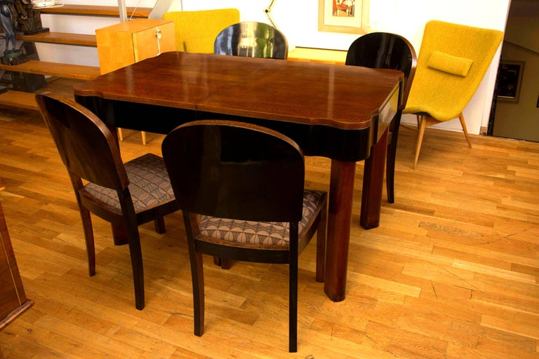 This very elegant dining set seats four people and features an adjustable oak dining table with four chairs. It has been made in Germany in the 1930s. The set has been professionally renovated; the wood has been polished to a high gloss using