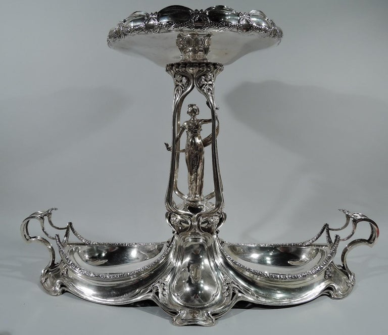German Art Nouveau 800 silver centerpiece. Made by M. H. Wilkens & Söhne in Germany, circa 1900. Shaped base with ovoid wells. Flying anthropomorphic end handles with pendant garlands. Central open pergola with figure of bare-breasted Classical