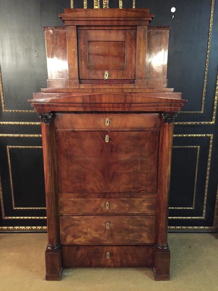 Early 19th century Biedermeier secretary cabinet composed of mahogany and featuring a series of drawers and on the top is a door as well as carved Corinthian column decorations.