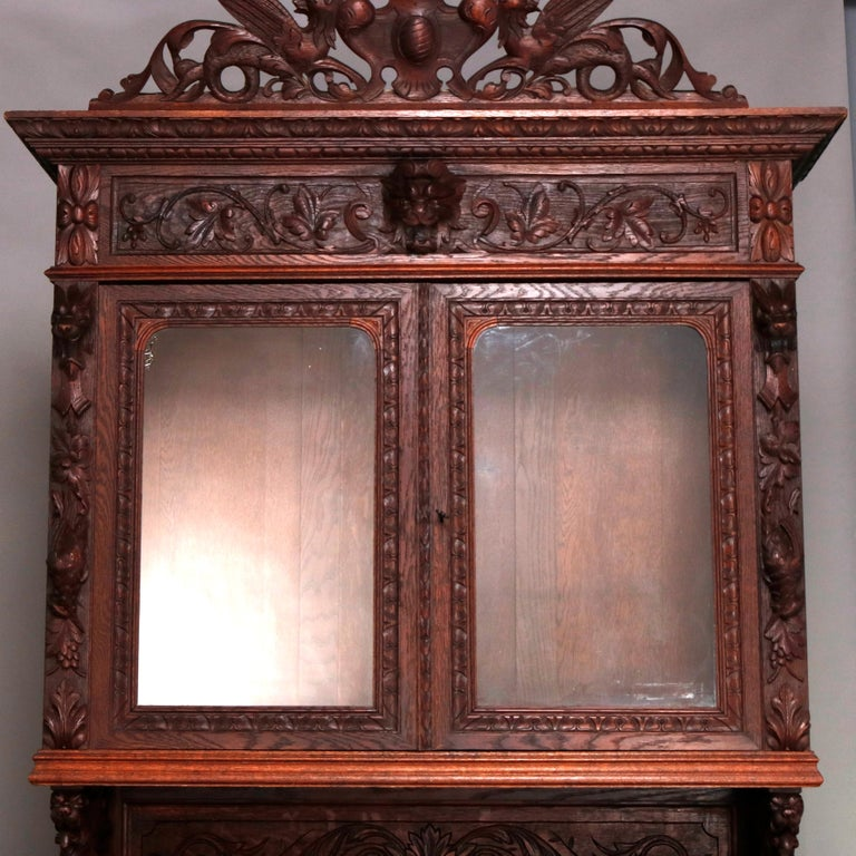 An antique German Black Forest figural hunt board breakfront cabinet offers oak construction with carved crest having central urn with flanking griffins and foliate decoration surmounting upper cabinet with double glass doors with carved griffin