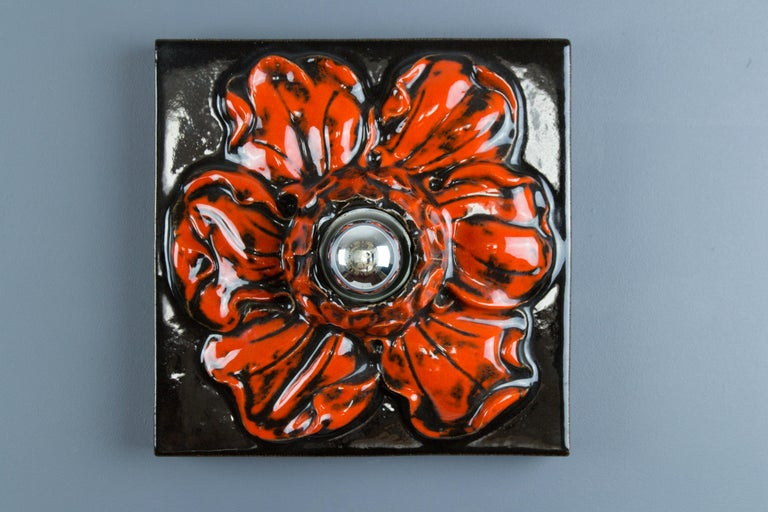 Beautiful ceramic square red wall lamp in the shape of a flower, made in Germany, in the 1960s. The mirror top light bulb is giving it a stunning light effect. The flower shaped lamp can be used as a wall or table lamp or ceiling light fixture. One