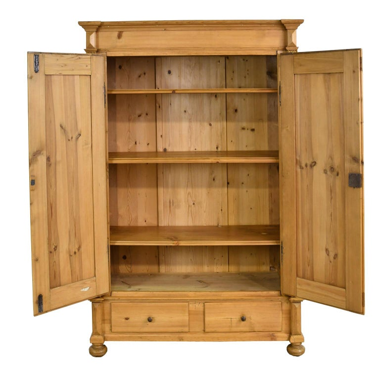A German Gründerzeit armoire in scrubbed pine with two doors that have raised panels and open to three adjustable interior shelves, with two exterior storage drawers along the bottom. Offers all the original components including period hardware with