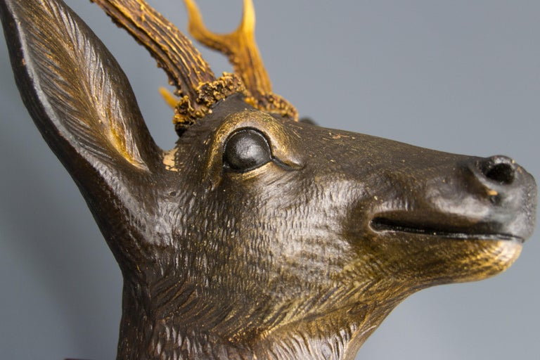 An adorable hand carved wall hanging deer head with genuine antlers mounted on a carved oval ornate wooden plaque. The deer sculpture is really awesome, masterfully crafted and it will be an expressive wall decoration, Germany, 1920s. Dimensions:
