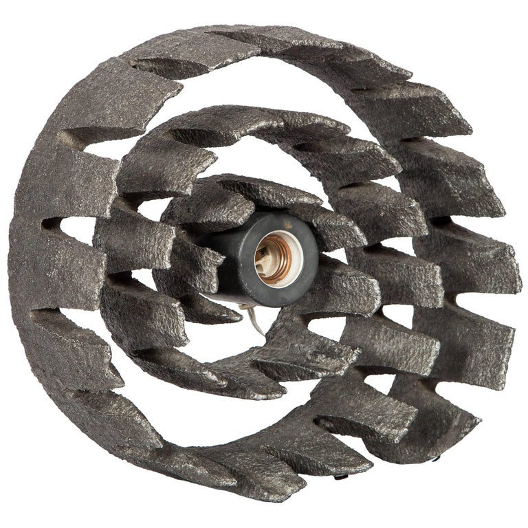 Mid-Century Modern lamp and sculpture. Brutalist design in textured hand-forged cast iron metal frame with spiral wheel formation. Single Light bulb and socket easily removable, converts the piece from functional light fixture to art sculpture.