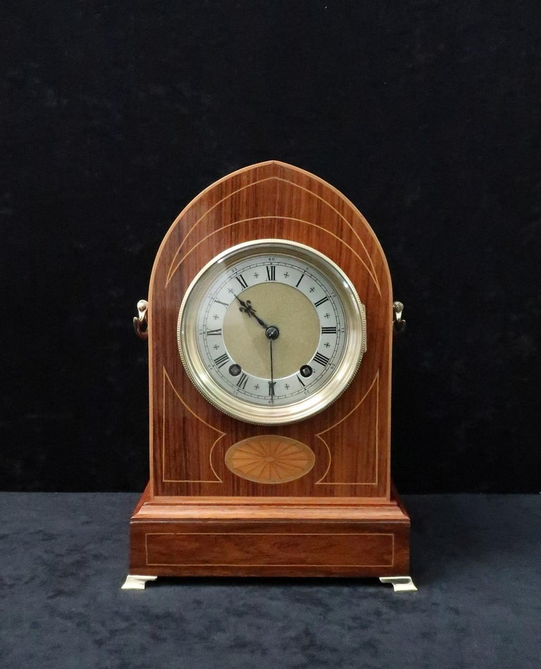 A very good quality German figured rosewood lancet shaped mantel clock with boxwood stringing and fan inlay to the front of the case and brass carrying handles to the sides. The clock has a brass dial with silvered chapter ring and an eight day