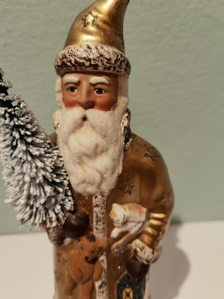 Santa Claus figure in hand painted gold papier mâché decorated with stars and a hand painted detailed face holding a tree. The Santa Claus is handmade in a original antique mould in Germany.