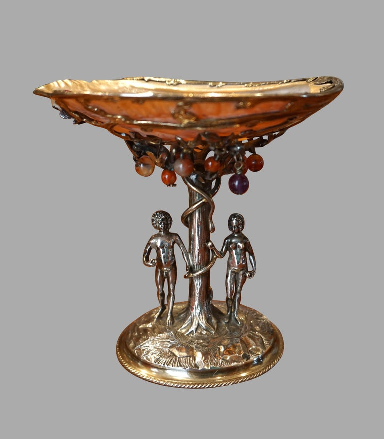 A finely executed silver tazza depicting Adam and Eve in the garden of Eden under the apple tree of knowledge wrapped by a snake. Above their heads is an open abalone shell decorated with semi-precious stones representing apples hanging from the