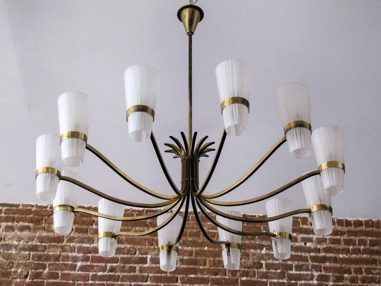 Stunning large decorative German twelve-arm brass chandelier, with two-tone brass arms and textured glass cups, wired for US standards, twelve E12 sockets, max. wattage 25w per socket, bulbs provided as a onetime courtesy.