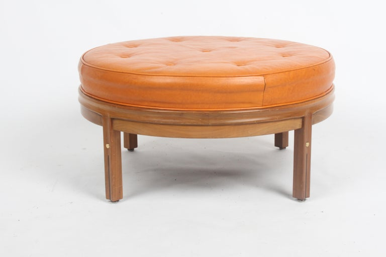 All original Mid-Century Modern round orange leather ottoman on sculpted wood base with tufted seat, designed by Gerry Zanck for Gregori furniture of Shelbyville, Indiana. Sculpted wood frame, with brass inserts and black inlay on legs. Original
