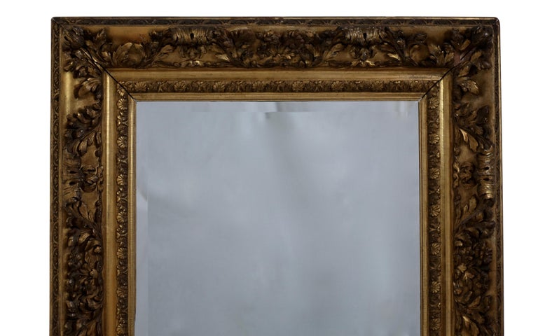 Unique gesso and carved gilt frame of flowers and acanthus leaves with a beveled glass mirror. English, 19th century. Label on the reverse. Mirror of later date.