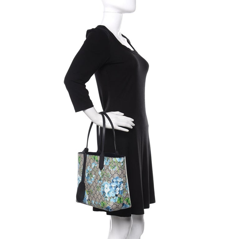 We guarantee this is an authentic GUCCI GG Supreme Monogram Blooms Print Small Reversible Tote Blue or 100% of your money back. This stylish tote is crafted of GUCCI GG Supreme Monogram canvas with Blue and White Blooming Flowers. The bag features