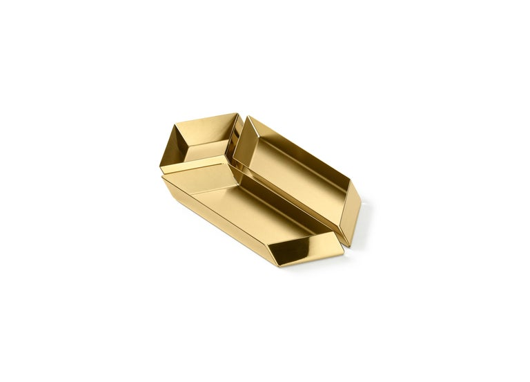The compositional scheme of this family of small trays is the axonometric isometric projection of two parallelepipeds which creates a three-dimensional optical effect implemented by inclined edges and by contrasting metal finishes. Like in a game,