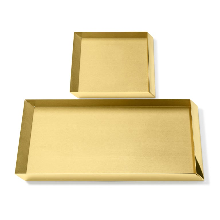Trays in brass. The compositional scheme of this family of small trays is the axonometric isometric projection of two parallelepipeds which creates a three-dimensional optical effect implemented by inclined edges and by contrasting metal finishes.