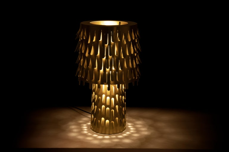 The lamp is made of polished brass, synonymous of elegance and preciousness. It is composed of two overlapping cylinders, the large stem supports an important lampshade decorated with a thousand leaves bent by the wind. The perforated structure and