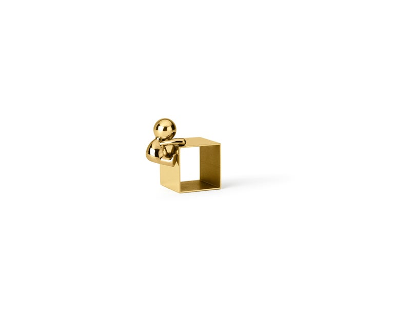 Napkin holder in brass Omini is a family of products that plays on the inclusion and the relationship between the human figure with a series of monolithic objects from geometric and Minimalist design. Small lilliputians attack and animate the pure