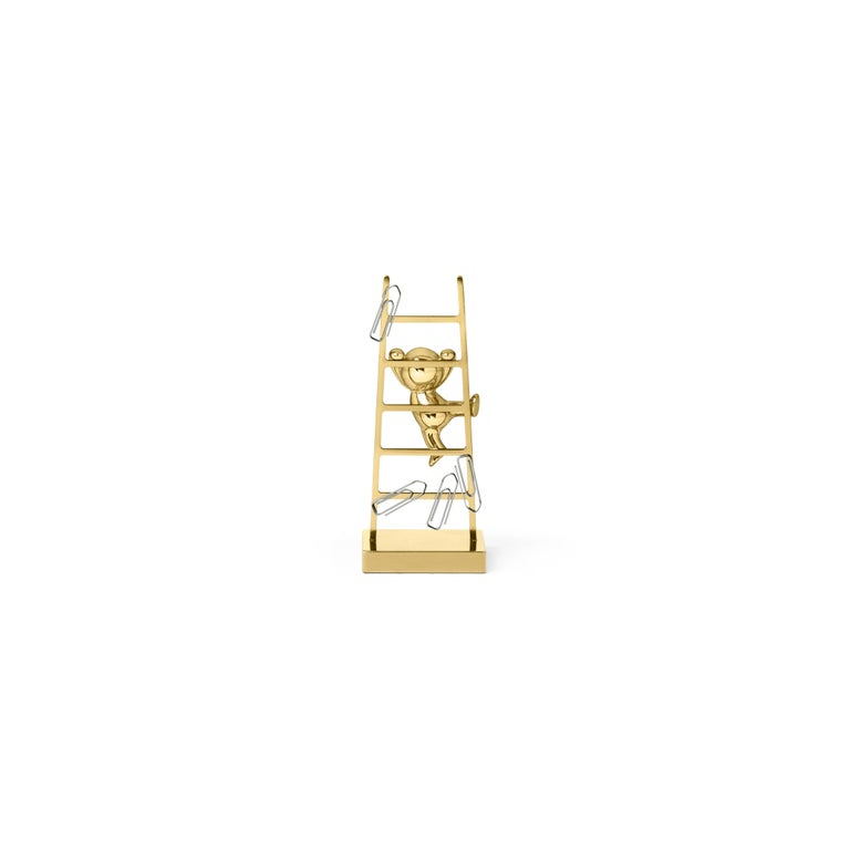 This unconventional paperclip holder is made of brass. This versatile piece features a small, stylized man climbing up a ladder that contains magnets, ensuring that all unruly paperclips scattered across a desk are well stored in one place.