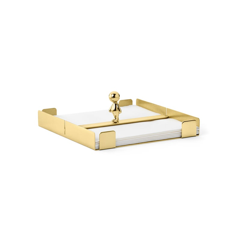 Napkins holder in brass Omini is a family of products that plays on the inclusion and the relationship between the human figure with a series of monolithic objects from geometric and Minimalist design. Small Lilliputians attack and animate the pure