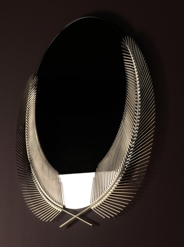 Mirror with palm leaves in brass. The round mirror surface is sunk into the graphic embrace of two palm fronds. The Sunset mirror is wall-mounted declaration of the true summer paradise scenario that lingers just below the surface of the present
