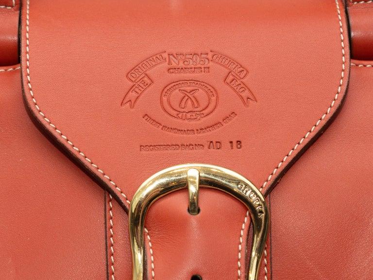 Product details: Orange large leather handbag by Ghurka. Interior zip pocket. Wooden detailing at dual top handles. Buckle closure at top. 15