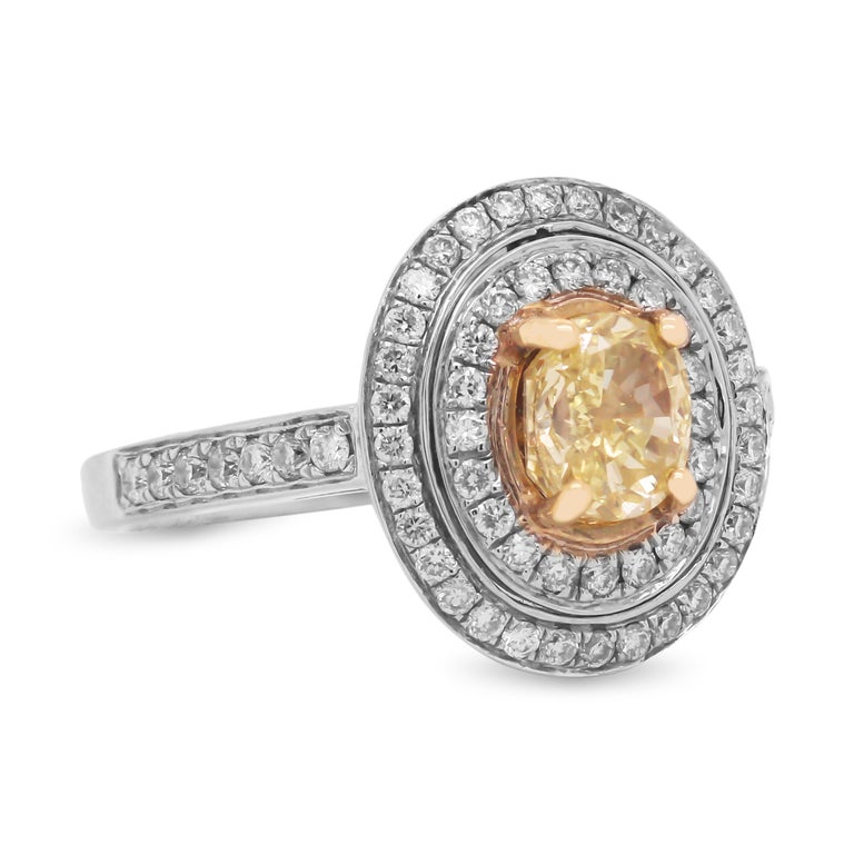 GIA 1.06 Carat VS1 Fancy Intense Yellow Diamond Ring with Diamonds Set in 18K White Gold  This oval Fancy Intense Yellow Diamond is a beautiful everyday ring with its natural beauty. Double halo mounting set with two rows of diamonds along with half