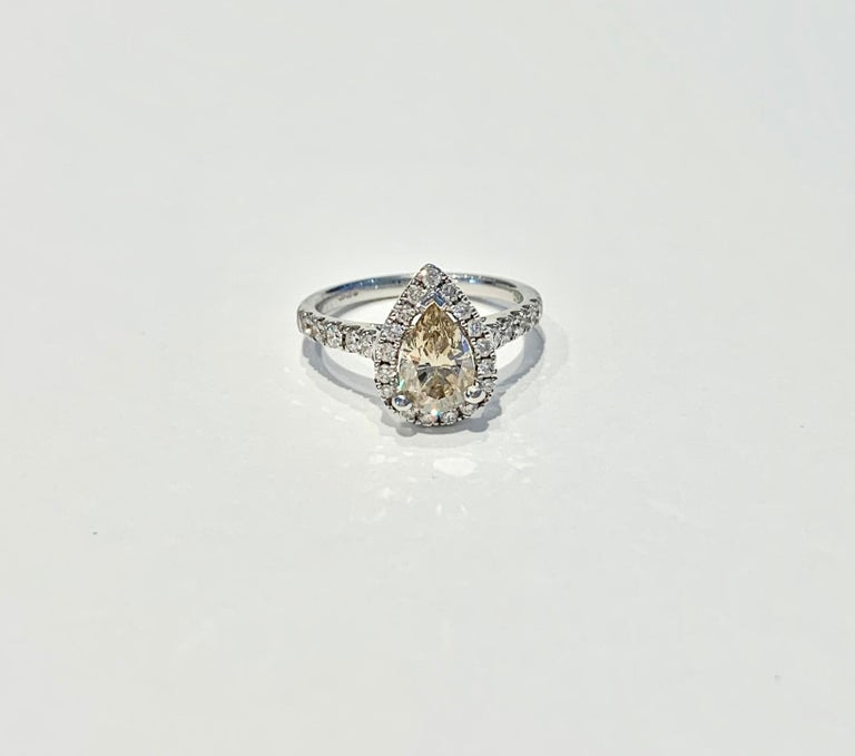 GIA Certified 1.07ct Fancy Brown/Yellow* Pear Cut diamond, set in a diamond halo design in 18ct White Gold.  There is amazing scintillation from both the Pear Cut diamond and the diamonds in the Halo and band.  This ring could make a unique