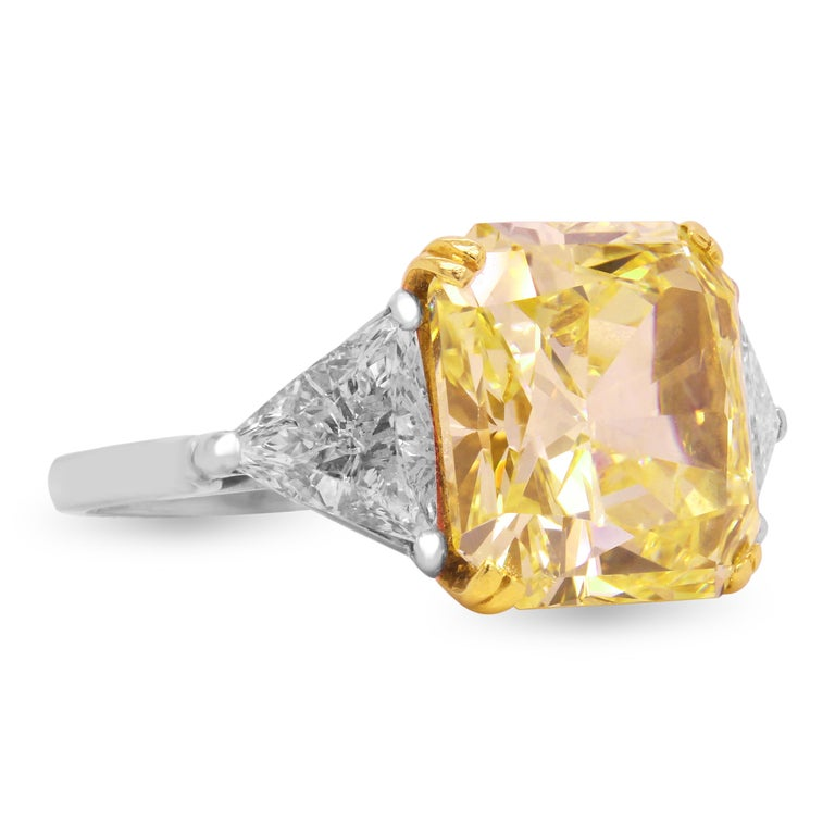 GIA Certified 11.22 Carat VVS1 Fancy Intense Yellow Diamond with Two Trillion Cut Diamonds set in Platinum  This exceptional Yellow diamond is beyond remarkable.  GIA Certified. Report Number: 11598214 11.22 carat. VVS1 Clarity. Natural Fancy