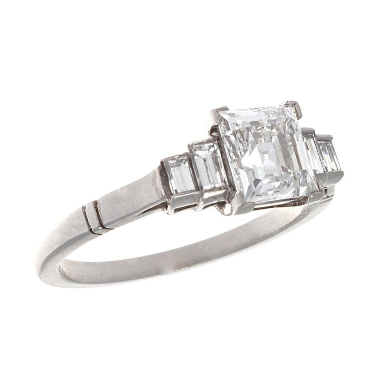 When you want a beautiful emerald cut diamond that reminds you of lightness and joy, you choose the setting that is in accord with such ideals. Featuring a GIA 1.17 carat Carre cut diamond, E color, VVS2 clarity, classic Art Deco lines, and